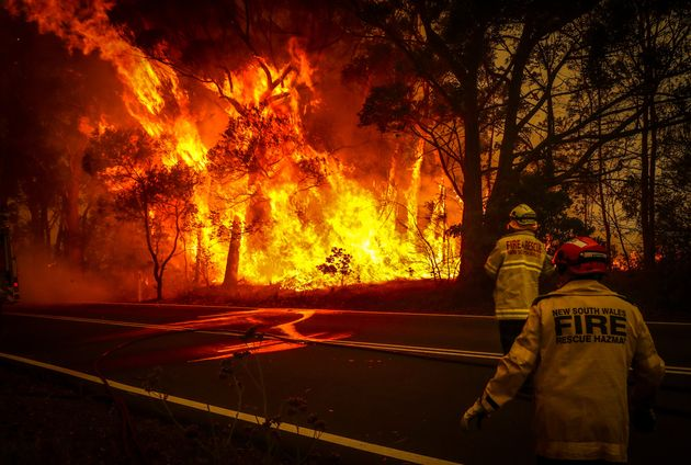Fire and rescue personnel watch a bushfire as it burns near homes on the outskirts of the town of Bilpin...