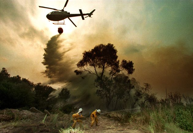 Two firemen fight a bushfire as a helicopter drops water on the blaze in the southern Sydney suburb of...