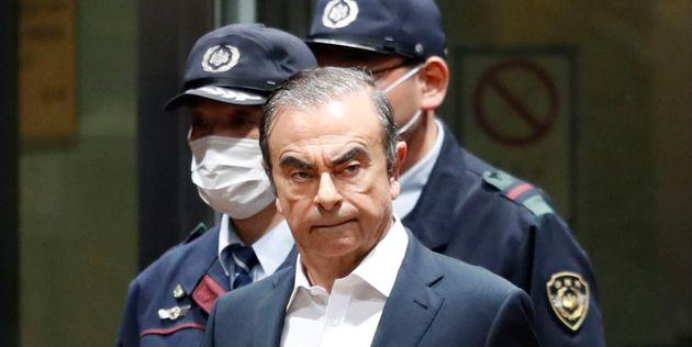 Former Nissan Chairman Carlos Ghosn, center, leaves Tokyo Detention Center in Tokyo, Thursday, April...