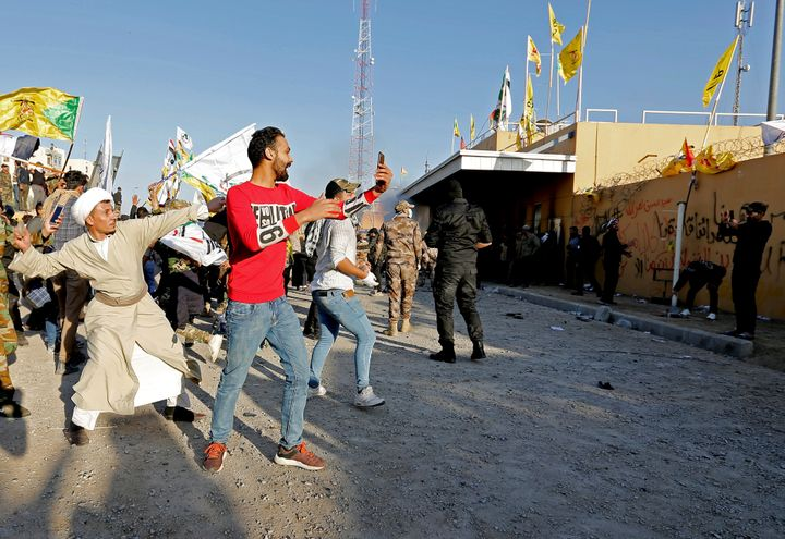 Demonstrators and militia fighters throw stones toward the U.S. Embassy in Baghdad on Dec. 31 during a protest to condemn air