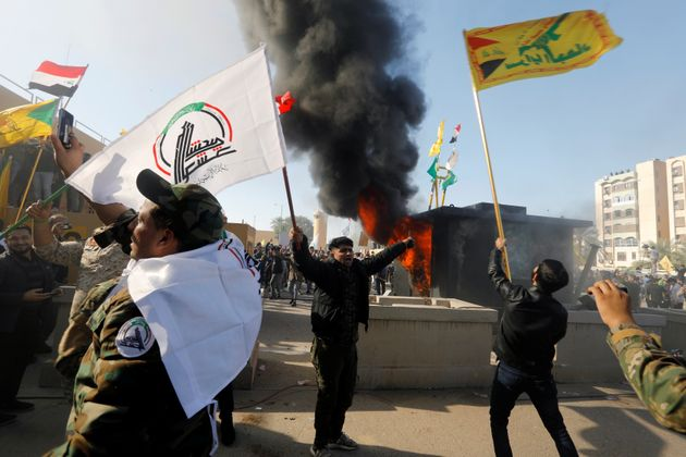 Protesters and militia fighters set on fire a security building of the U.S. Embassy, as people gather...