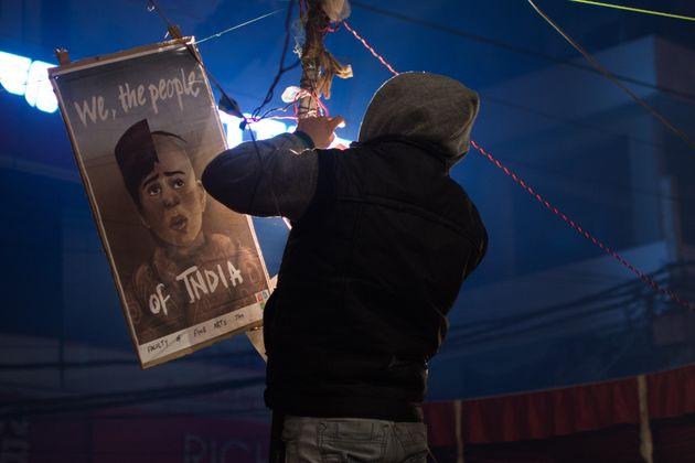 A man hangs a banner at the sit-in protest against the Citizenship Amendment Act 2019 in Shaheen Bagh,...