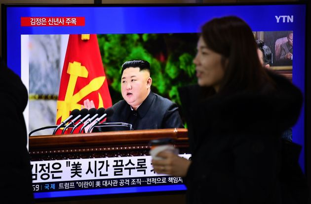 A woman walks past a television news programme showing file footage of North Korean leader Kim Jong Un,...