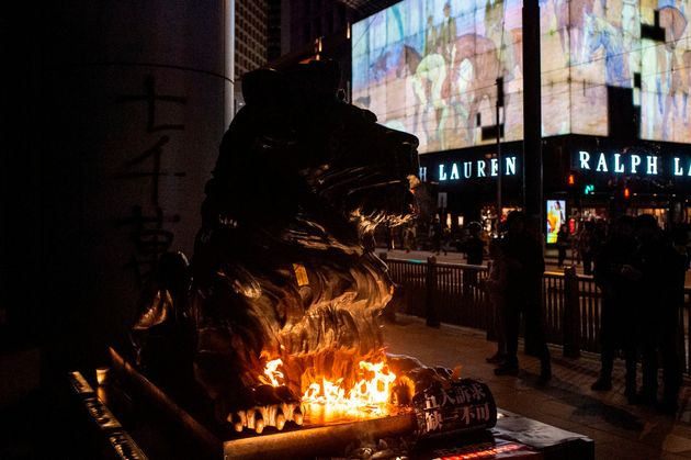 An HSBC lion statue is set on fire by a protester outside the bank's headquarters in Central area following...