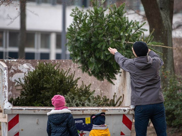 30 December 2019, Saxony, Dresden: A man throws his Christmas tree into a specially erected container while his children watch him. Until 11 January 2020, citizens can dispose of their Christmas trees free of charge. The Department for City Greenery and Waste Management is setting up over 100 collection points throughout the city. Photo: Robert Michael/dpa-Zentralbild/dpa (Photo by Robert Michael/picture alliance via Getty Images)