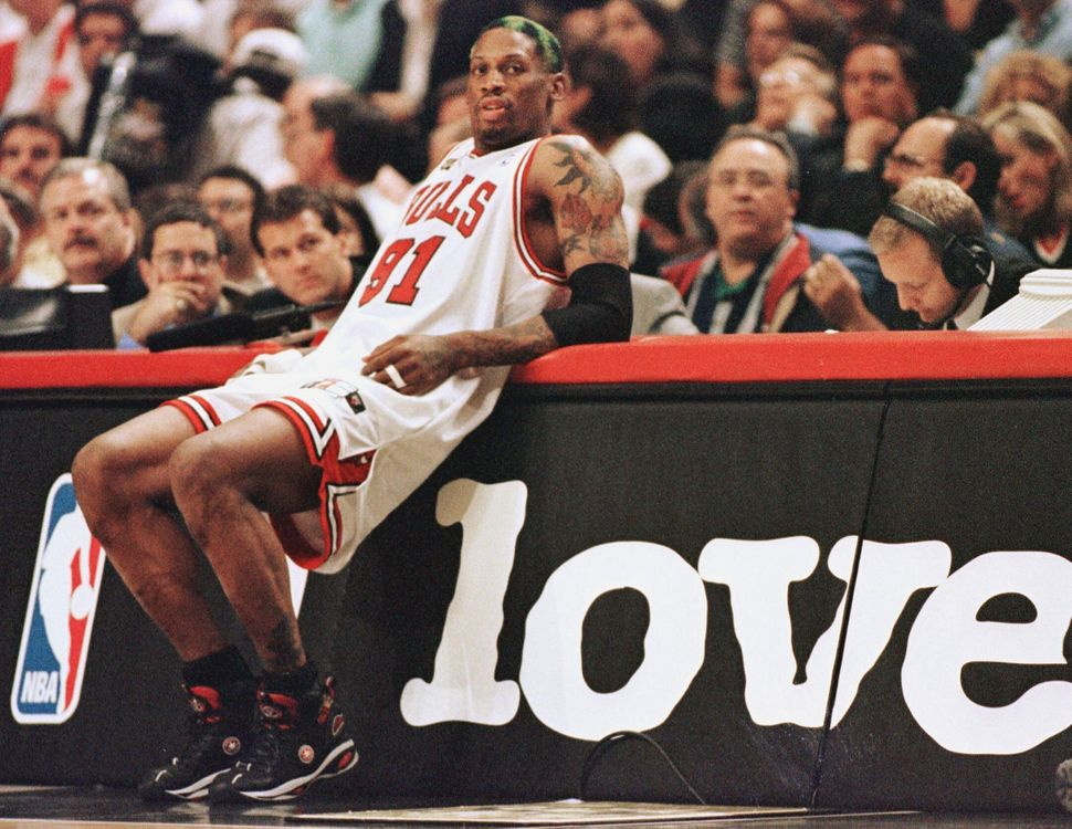 Rodman leans on the scorers' table as he waits to come into the game against the Utah Jazz in game four of the NBA Finals on