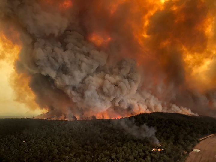 Wildfires rage under plumes of smoke in Bairnsdale, Australia, on Monday. Thousands of tourists fled Australia's wildfire-rav