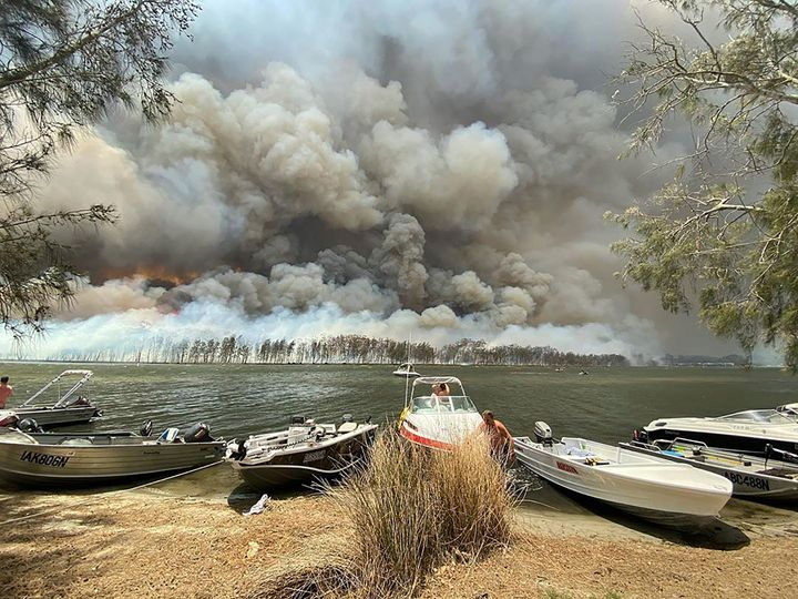 Boats are pulled ashore as smoke and wildfires rage behind Lake Conjola, Australia, on Thursday.