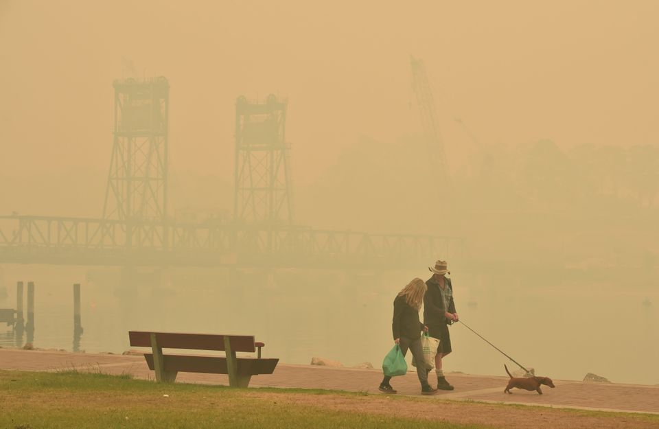 Tourists walk with a dog through dense smoke from bushfires in front of the Batemans Bay bridge as cars...