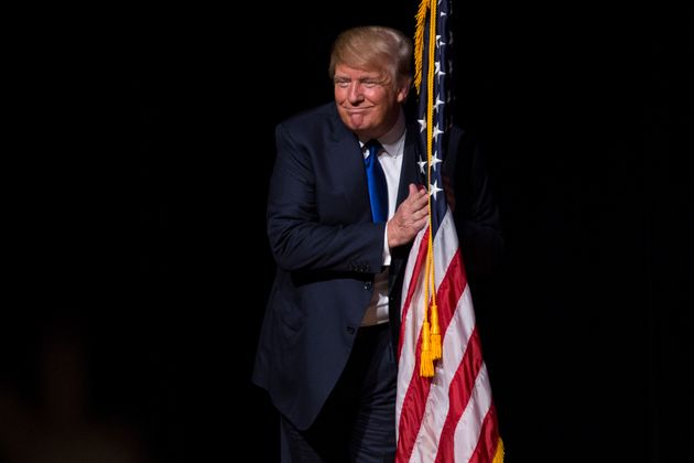 DERRY, NH - AUGUST 19: U.S. Republican presidential candidate Donald Trump hugs an American flag as he...