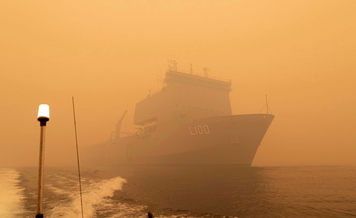 In this photo released and taken Jan. 2, 2020, by the Australian Department of Defense, the HMAS Choules sails off the coast of Mallacoota, Victoria to supply support to people cut off by bush fires. Navy ships plucked hundreds of people from beaches and tens of thousands were urged to flee before hot weather and strong winds in the forecast worsen Australia's already-devastating wildfires. (Australian Department of Defense via AP)