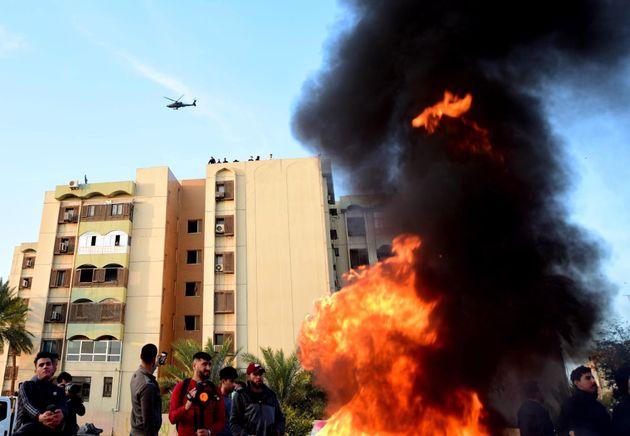 Un helicóptero estadounidense AH-64E Apache sobrevuela una manifestación de la agrupación armada iraquí...