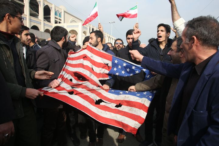 Iranians tear up an American flag during the protests.