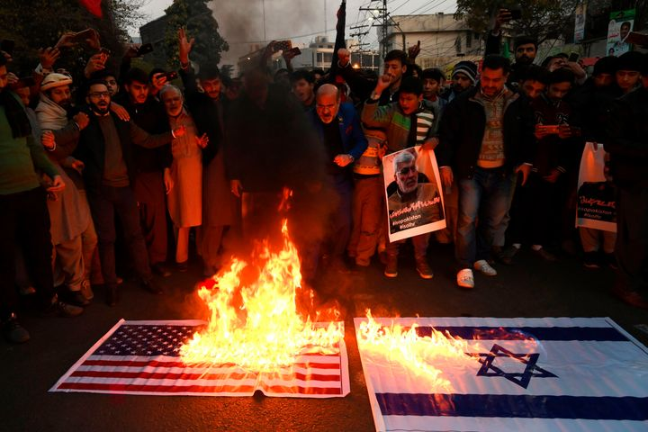 Protesters in Lahore burn American and Israeli flags.