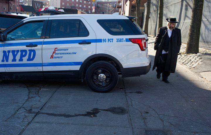 A Hasidic man walks past a police patrol car on Dec. 12 in the Williamsburg neighborhood of Brooklyn. Hasidic leaders have as