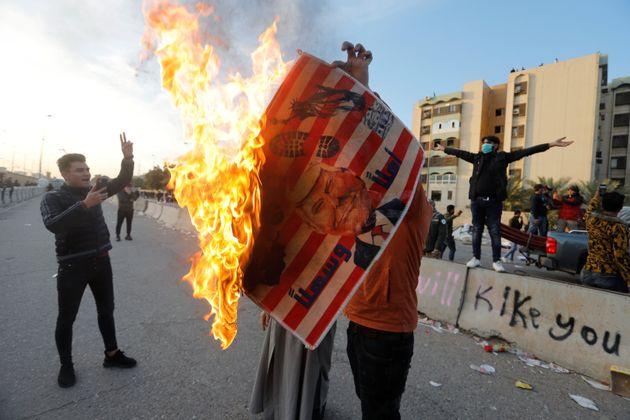 Un manifestant tient une pancarte avec l'illustration du président américain Donald Trump...