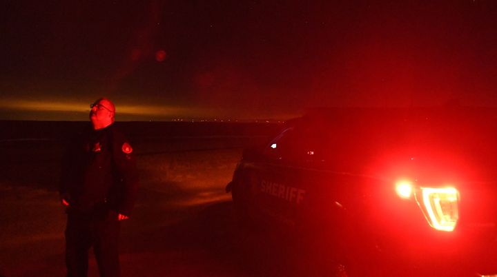 Lincoln County Sheriff's Deputy Justin Allen stands outside of his squad car looking at the night sky near Limon, Colorado, o