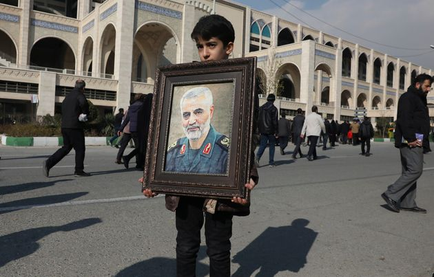 A boy carries a portrait of Iranian Revolutionary Guard Gen. Qassem Soleimani, who was killed in the...