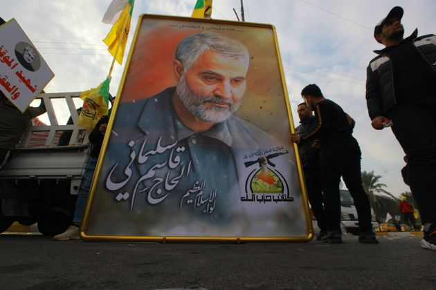 Mourners stand next to a giant portrait for Qassem Soleimani during a funeral