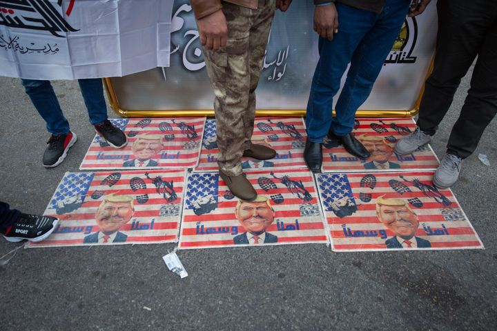 Mourners step over a U.S. flags with pictures of President Donald Trump during the funeral procession for Iran's top general