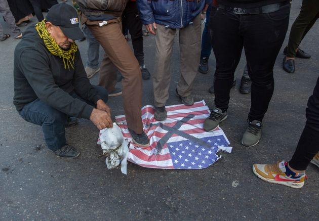 Mourners step over a U.S. flag before burning it during the funeral of Iran's top general Qassem