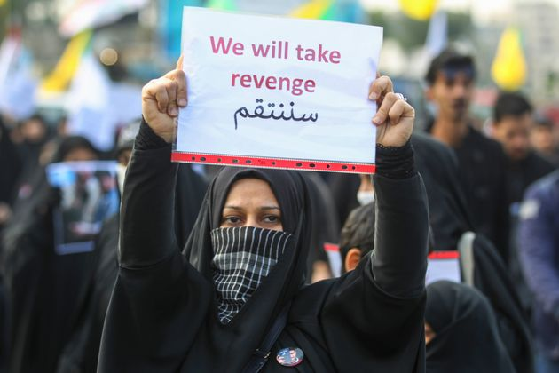 An Iraqi woman holds a placard during the funeral of Iranian military commander Qasem