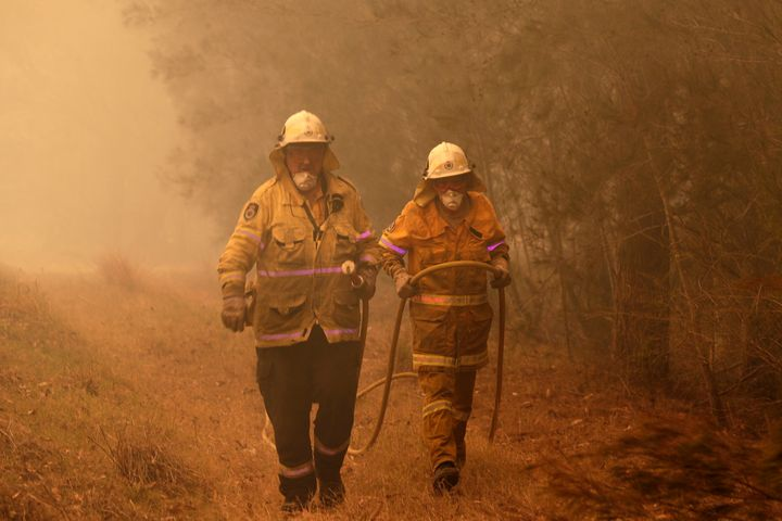 Firefighters drag their water hose after putting out a spot fire near Moruya, Australia, Saturday, Jan. 4, 2020.