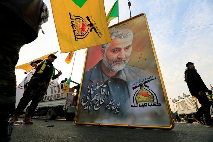 Members of the Kataib Hezbollah Iraqi militia hold a picture of Iranian Maj. Gen. Qassem Soleimani on Jan 4. in Baghdad as th