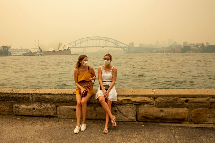 German tourists Julia Wasmiller (left) and Jessica Pryor look on at Mrs Macquarie's chair, wearing face masks due to heavy sm