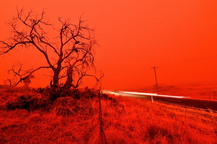 A long exposure picture shows a car commuting on a road as the sky turns red from smoke of the Snowy Valley bushfire on the o
