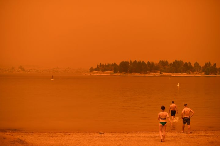 Residents take a dip to cool down at Lake Jindabyne, under a red sky due to smoke from bushfires, in the town of Jindabyne in