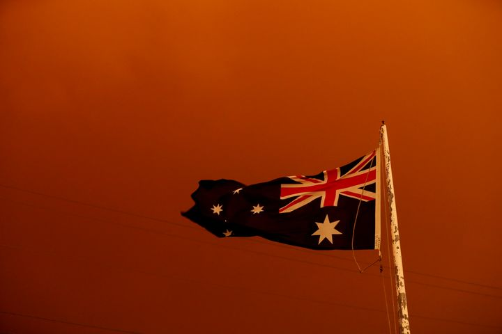 The Australia flag flies under red skies from the fires on Jan. 4 in Bruthen, Australia. Two people are dead and 28 remain mi