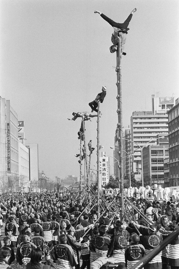 出初め式ではしご乗りの妙技を披露する江戸消防記念会の人たち(東京・中央区晴海の中央通り)
