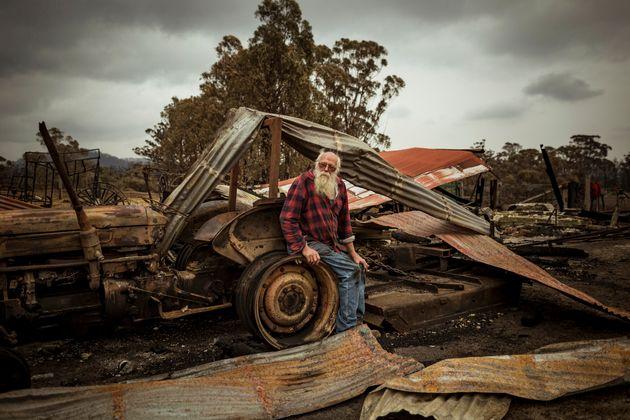Un hombre entre restos calcinados por la ola de incendios en
