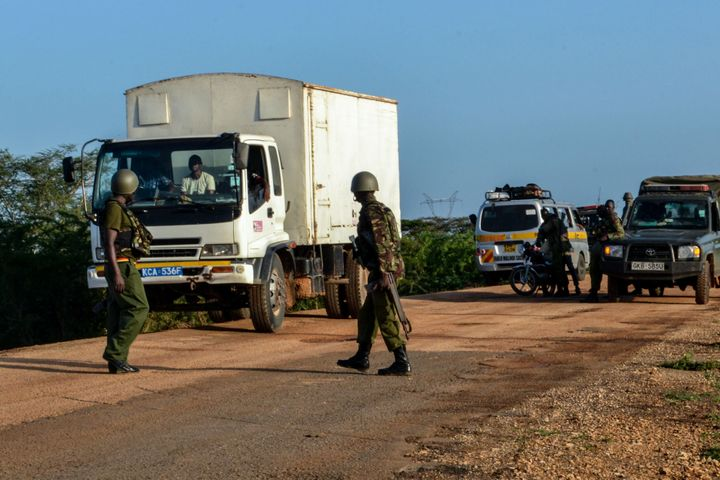 Kenyan police officers check vehicles on a road after a bus, traveling from the coastal region of Lamu to the town of Malindi