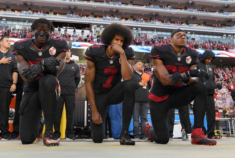 Teammates Eli Harold, Kaepernick and Eric Reid kneel in protest during the national anthem prior to a game against the Arizon