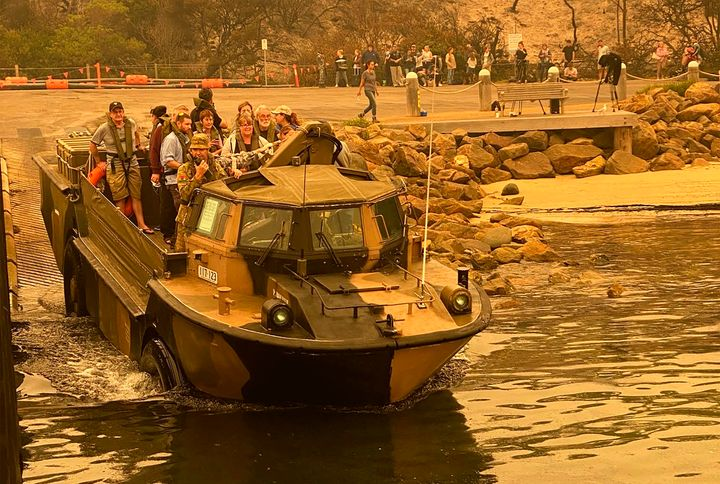 In this photo released and taken Jan. 2, 2020, by the Australian Department of Defense, evacuees are transported  in a lighter, amphibious, resupply, cargo (LARC) transport amphibious vehicle, from Mallacoota, Victoria, Australia. Navy ships plucked hundreds of people from beaches and tens of thousands were urged to flee before hot weather and strong winds in the forecast worsen Australia's already-devastating wildfires. (Australia Department of Defense via AP)