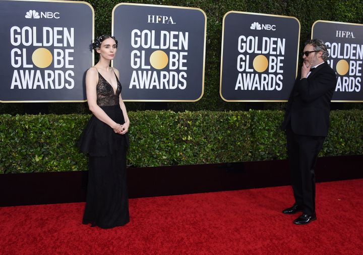 Rooney Mara, left, walks on the red carpet as Joaquin Phoenix looks on at the 77th annual Golden Globe Awards at the Beverly