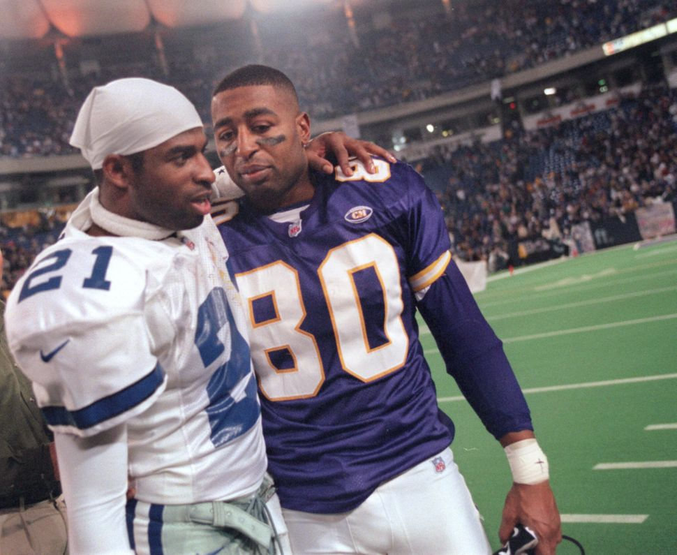 Sanders of the Dallas Cowboys (left) and Minnesota Vikings wide receiver Cris Carter greet each other following a Vikings pla