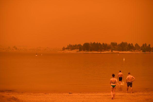 뉴사우스웨일스주 진다바인 주민들이 진다바인 호수로 들어가고 있다. 들불 연기로 인해 하늘이 빨갛다. 1월