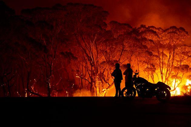 오스트레일리아 타부리 호수에서 불타는 관목을 지켜보는 주민들. 1월 4일. 12월 30일 이후 뉴사우스웨일스에서는 최소 8명의 사망자가 발생했고 주택 1,365채가