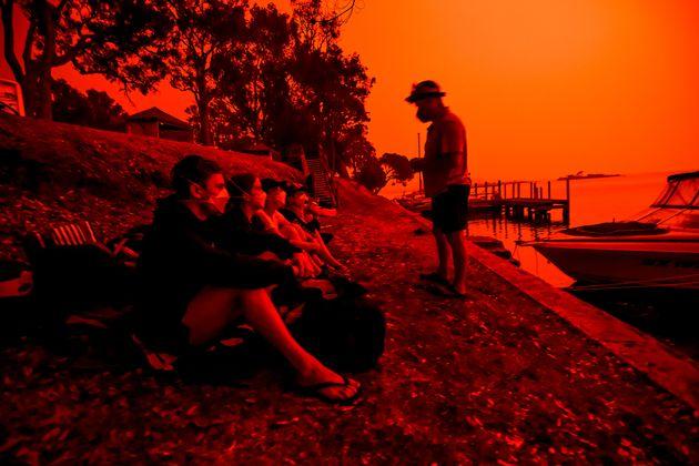 부모가 아이들에게 불길이 마을쪽을 향하고 있지 않다고 안심시키고 있다. 오스트레일리아 말라쿠타, 1월 4일. 하늘이 빨갛다. 학교에 다닐 연령 이상의 아이들만 배로 대피하는 것이 허용되어...