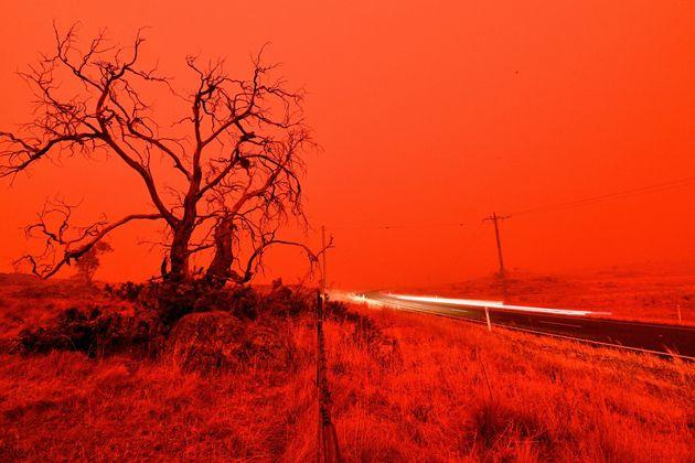쿠마 외곽 스노이 밸리 들불의 연기로 빨갛게 된 하늘과 운행 중인 차량을 담은 장노출 사진. 1월