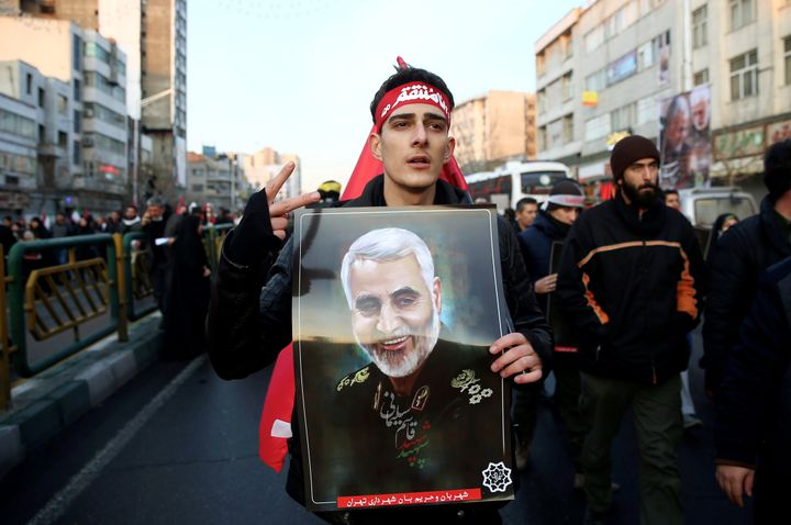 An Iranian man holds a picture of Qassem Soleimani during a funeral procession in Tehran on Jan. 6, 2020.