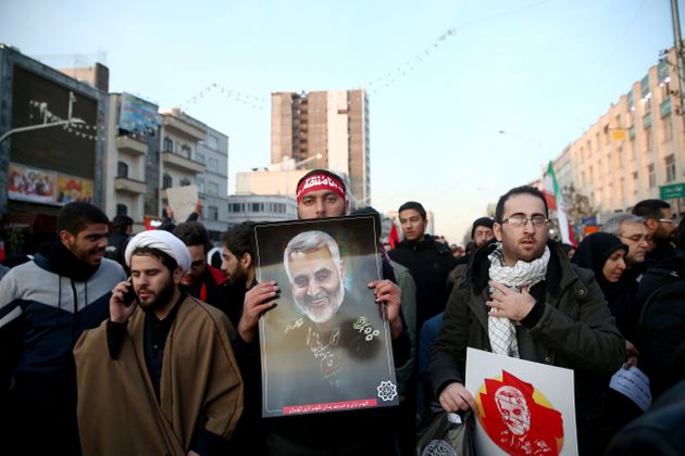 An Iranian man holds a picture of Qassem Soleimani during a funeral procession in Tehran, Iran on Jan....