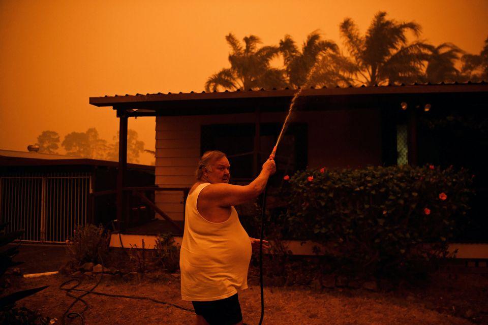 Homem usa mangueira para tentar conter fumaça em Nowra, New South