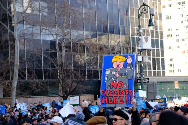Marchers hold a sign depicting Trump as a fascist during the rally against anti-Semitism.