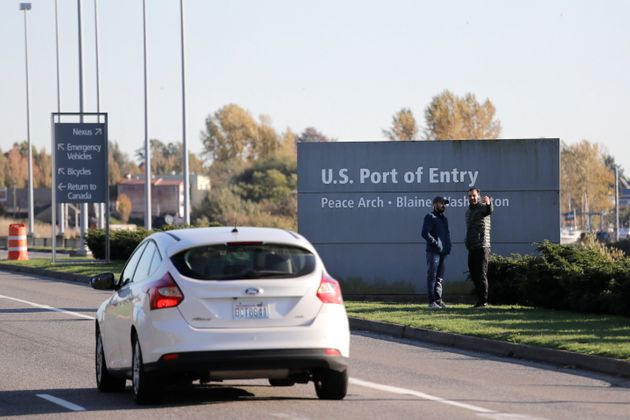 In this photo taken Oct. 9, 2019, pedestrians take a photo at an entry sign as traffic enters the United States from Canada at the Peace Arch Border Crossing, in Blaine, Wash.