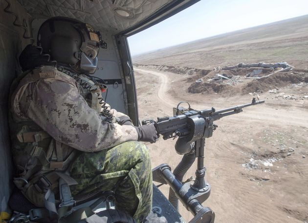 A Canadian Forces door gunner keeps watch as his Griffon helicopter goes on a mission, February 20, 2017...