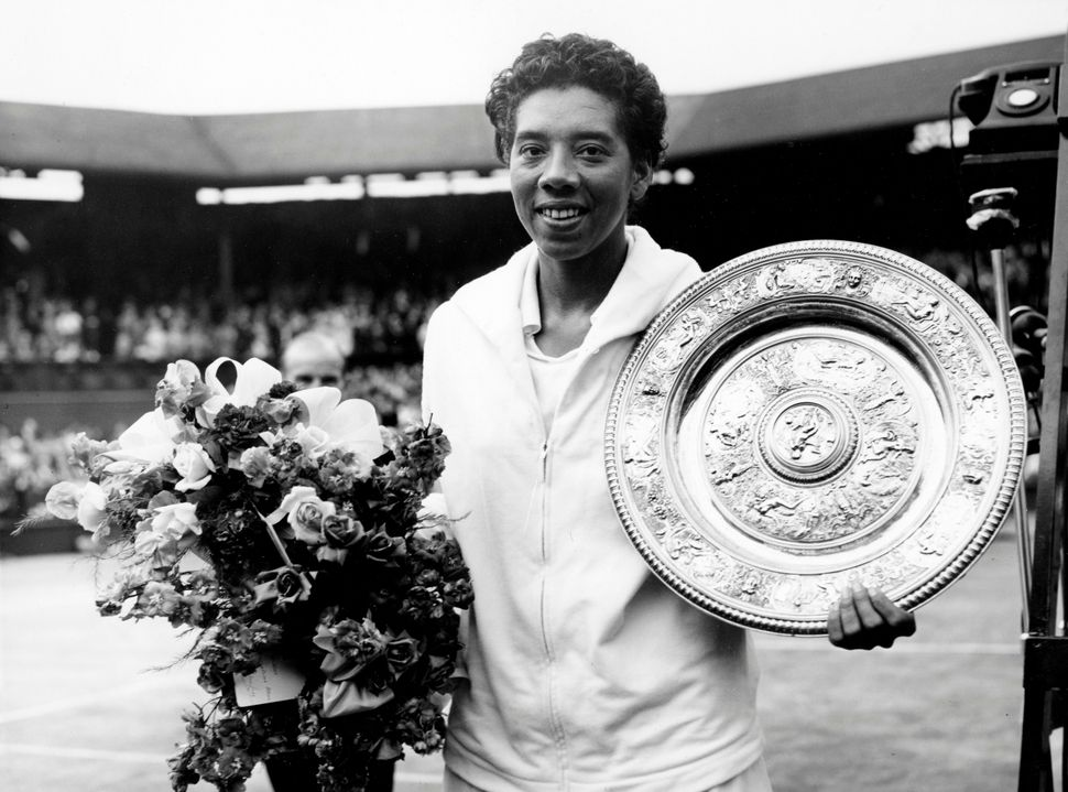 Althea Gibson holds her trophy after winning at Wimbledon on July 5, 1958.